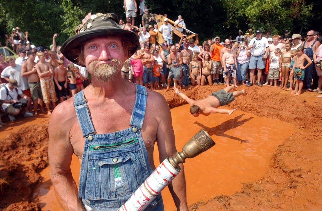 DUBLIN, GA - JULY 8: L-bow, the official mascot of the Summer Redneck Games, poses next to the mud pit with the ceremonial torch during the 11th annual games July 8, 2006 in Dublin, Georgia. Started in 1996 as a spoof for the summer Olympics held in Atlanta, the games feature bobbing for pigs feet, hub cap hurling and the Redneck mud pit belly flop contest for trophies. (Photo by Stephen Morton/Getty Images)