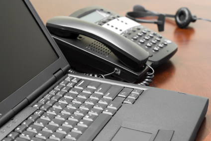 A black laptop computer in the foreground with a slightly out-of-focus business telephone and operator headset in the background.